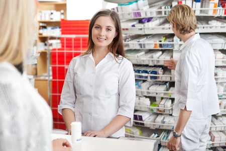technician: Pharmacist smiling while attending customer at counter