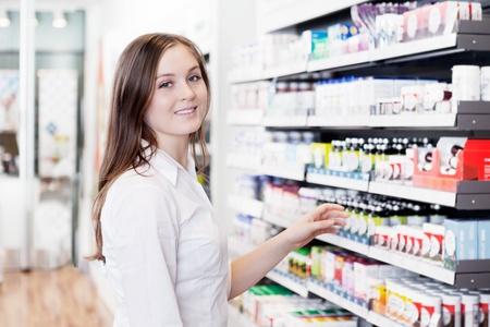 Retrato de joven farmacéutico de pie femenino en farmacia Foto de archivo