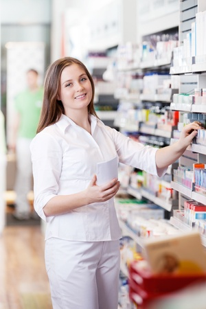 Portrait of female pharmacist standing in pharmacy drugstore with prescription paper Stock Photo - 12766433