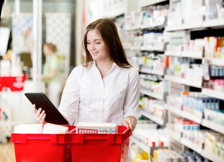Pharmacist filling prescriptions looking at digital tablet photo