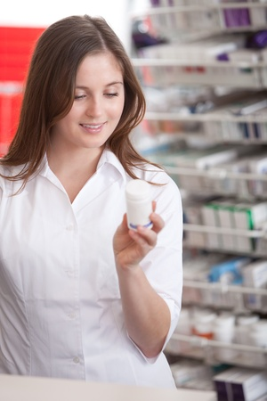 Portrait Of A Female Pharmacist At Pharmacy Reading Information On Medicine  photo