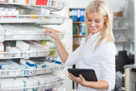 Female chemist standing in pharmacy drugstore with tablet PC photo