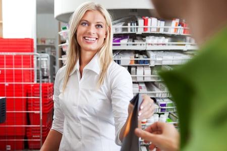 prescribe: Female Pharmacist With a Male Customer in Pharmacy Drugstore  Stock Photo