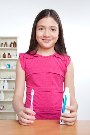 Portrait of girl holding toothbrush and tooth paste  photo