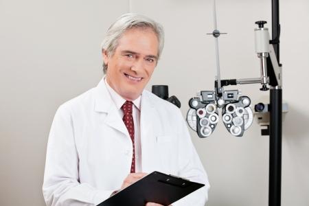 optometria: DoÅ›wiadczony okulista uÅ›miechajÄ…c siÄ™ z notatnika w jego klinice