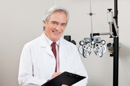 Experienced optometrist smiling with notepad in his clinic photo