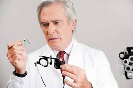 Skilled optometrist examining the lens while holding trial frame for an eye checkup photo