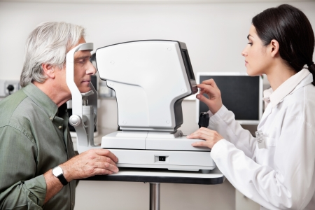 Young optometrist performing visual field test with an advance equipment photo