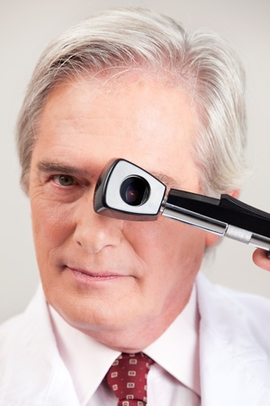glaucoma: Eye doctor optometrist with opthalmoscope