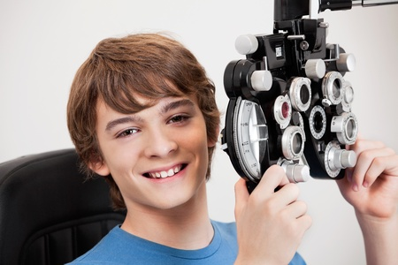 eye test: Smiling boy holding phoropter while undergoing an eye examination