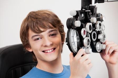 diopter: Sonriendo for�ptero muchacho que sostiene mientras se somete a un examen de los ojos
