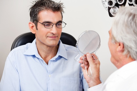 Man in stylish reading glasses while looking at mirror with optometrist in the clinic photo