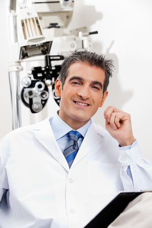 Portrait of a happy optometrist smiling while sitting in his office photo