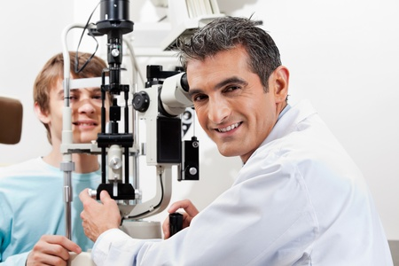oculist: Portrait of a smiling optometrist while performing visual field test on his patient