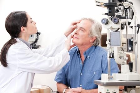 optometrist: Optometrist taking an eyesight test examination  Stock Photo