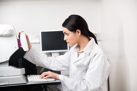 Young female optometrist concentrating while storing data from the equipment photo