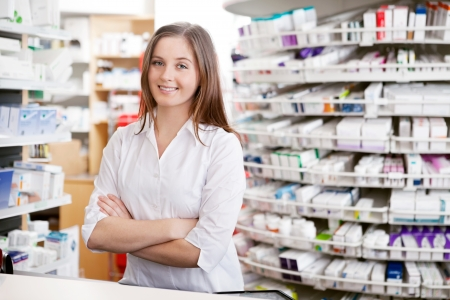 pharmacist: Portrait of female pharmacist standing with arms crossed at counter in pharmacy