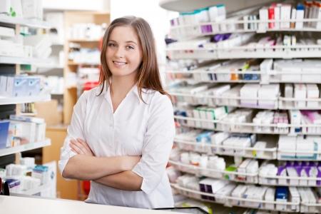 Retrato de mujer de pie farmacéutico con los brazos cruzados en el mostrador en farmacia Foto de archivo