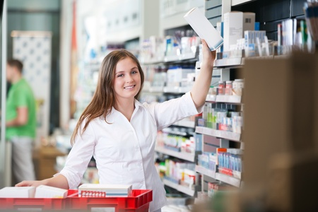 Portrait of female pharmacist keeping a box on shelf photo