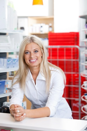 Portrait of smiling female chemist standing at counter photo