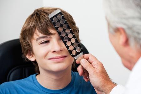 oculist: Mature optometrist checking eye through retinoscopy glasses at the clinic
