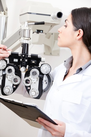 Female optometrist looking at phoropter  Stock Photo - 13264255