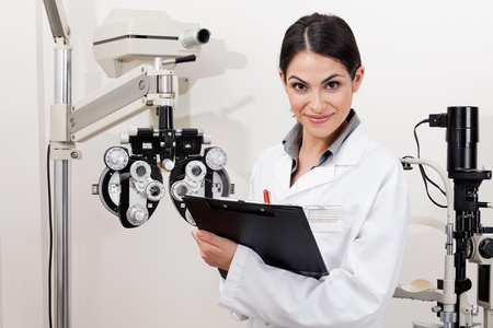 Portrait of a young optometrist smiling with clipboard at clinic photo