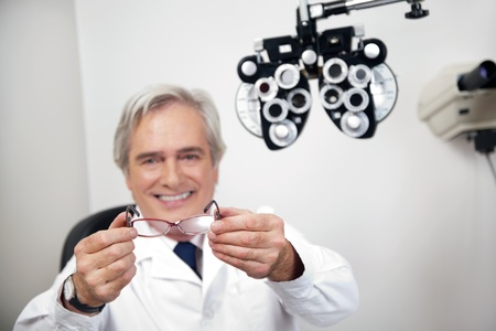 oculist: Portrait of smiling mature optometrist holding glasses at the clinic