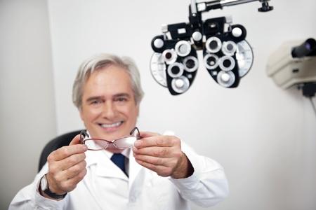 oculista: Retrato de la sonrisa optómetra madura la celebración de vasos en la clínica