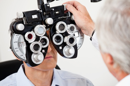 refractive: Optometrist performing eye test with phoropter on a male patient