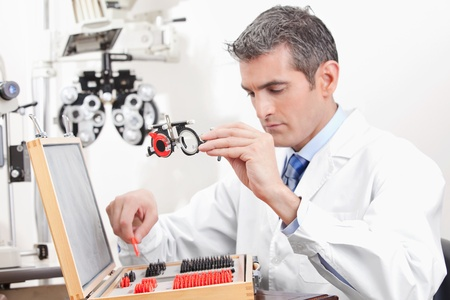 optical instrument: Optometrist looking at measuring eye glasses  Stock Photo