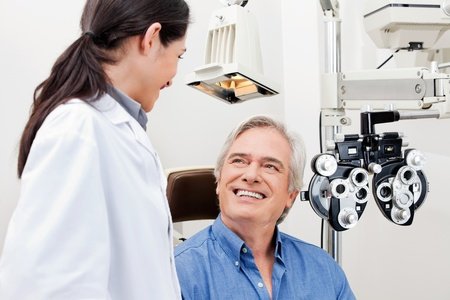 doctor exam: Smiling mature patient consulting with optometrist for an eye checkup