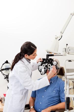 optometria: Kobieta optometrist wykonujÄ…c sprawdzanie wzrokowy z phoropter w klinice