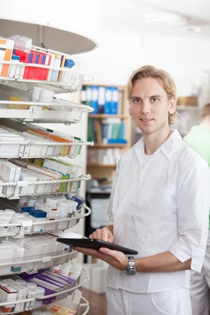 Portrait Of Smiling Male Pharmacist Holding Tablet Pc In Drugstore  photo