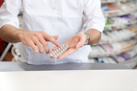 Male Pharmacist Giving Prescription Medicine In Pharmacy Drugstore  photo