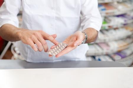 Male Pharmacist Giving Prescription Medicine In Pharmacy Drugstore  photo