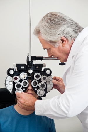 oculist: Mature experienced optometrist performing eye checkup with phoropter Stock Photo