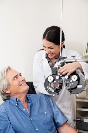 Caring eye specialist smiling at mature patient before performing eye test with phoropter photo