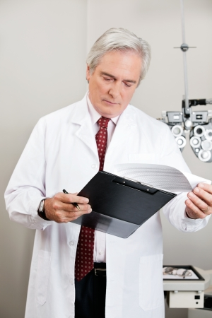 Busy optometrist checking the prescription in his clinic photo