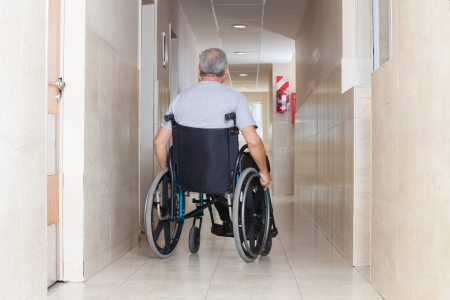Rear view of a senior man sitting in a wheelchair at hospital corridor photo