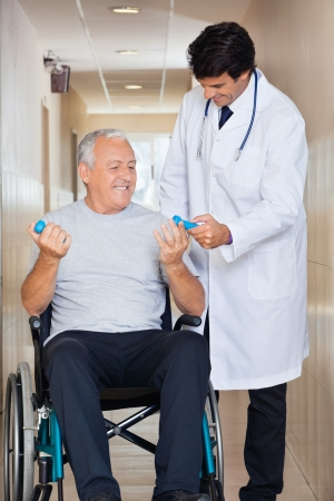 elderly exercise: Happy young doctor giving hand weights to the senior man sitting in a wheelchair at hospital