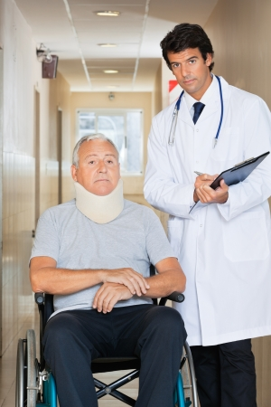 Young doctor writing on clipboard by senior man sitting on wheel chair with neck brace photo