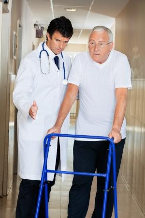 Doctor helping senior patient walk down hallway using Zimmer frame Stock Photo - 13800169