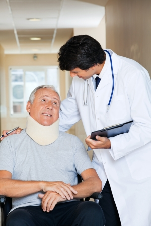 Friendly young doctor communicating with senior man sitting in wheel chair Stock Photo - 13800167
