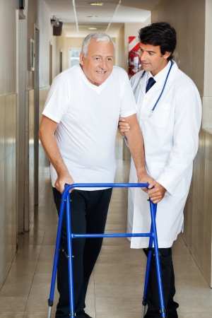 Happy senior man being helped by a male doctor to walk the Zimmer frame photo