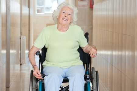 Happy senior woman sitting in a wheel chair at hospital corridor photo