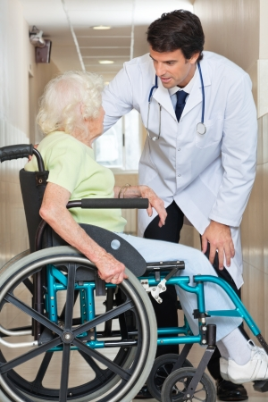 Young doctor communicating with senior female patient sitting in wheelchair at hospital photo