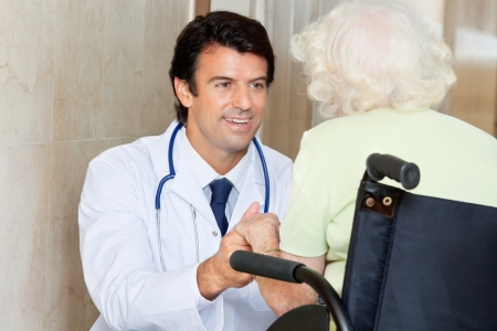 Happy young male doctor looking at senior woman sitting in wheel chair at hospital photo