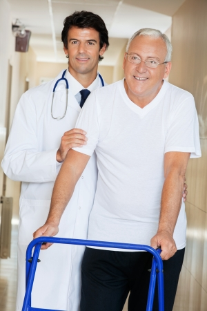 Young happy doctor helping an old man with his walker Stock Photo