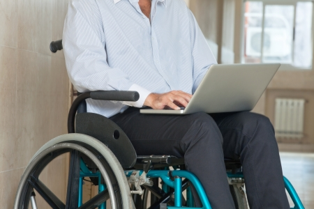 Mid section of a man sitting in wheel chair using laptop at hospital Stock Photo - 13800183